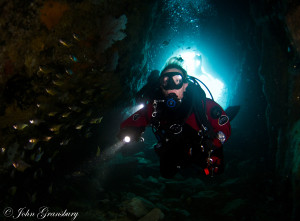 Diver in the shallow entrance, Fish Rock Cave, South West Rocks, NSW, Australia